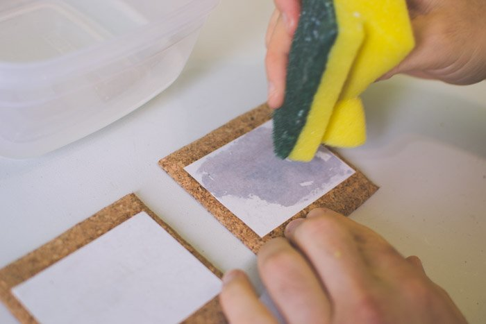 A close up photo of gluing photographs to coasters with a sponge. Unique photography ideas.