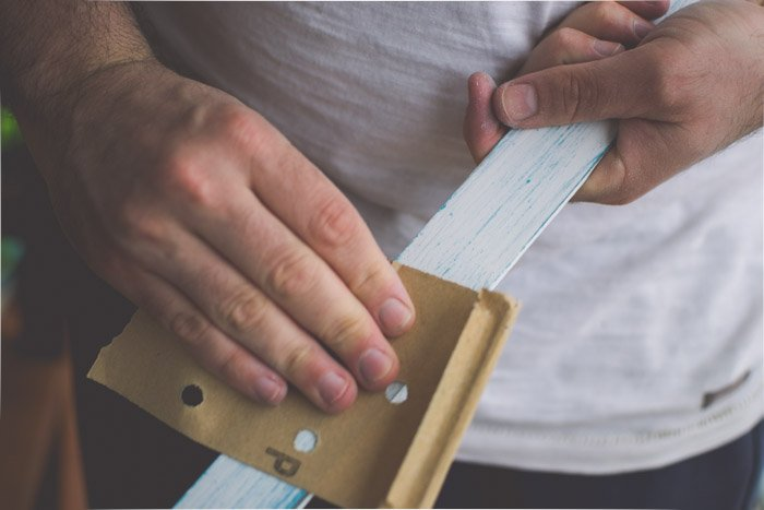 A close up of a hand sanding a wooden board. Creative photography ideas.