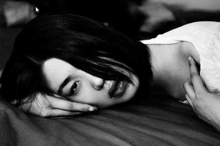 Andi Elloway black and white portrait of a girl on a bed. Famous Portrait Photographers