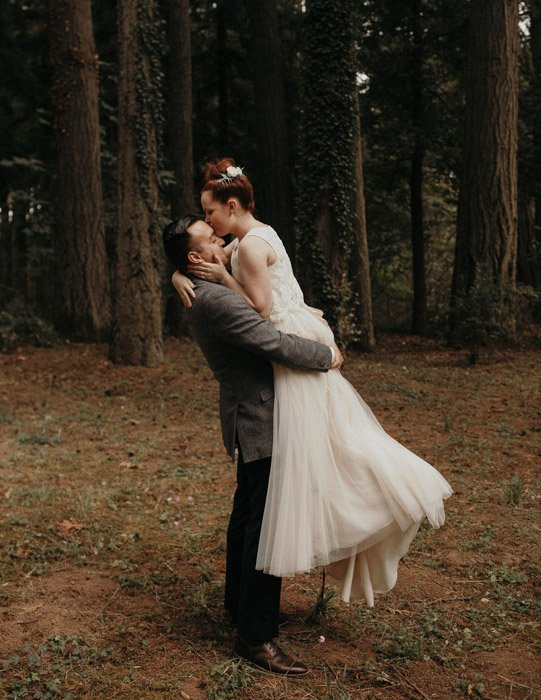 Jordan Voth wedding photography of a newlywed couple kissing in the woods. Famous Portrait Photographers