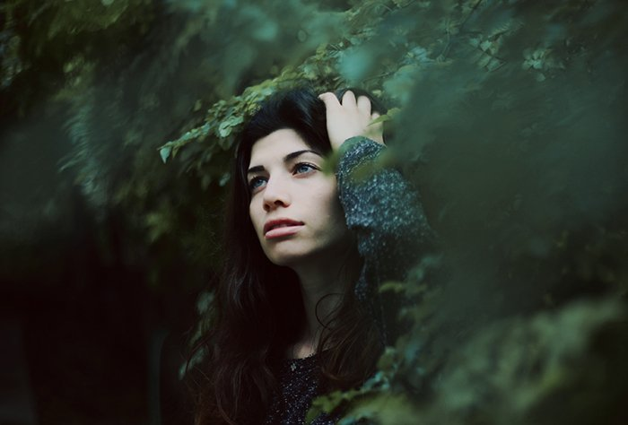 Mysterious portrait of a dark haired girl with a blurry forest background.