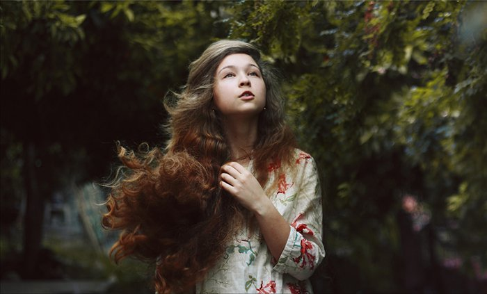 Portrait of a dark haired girl with a blurry forest background.