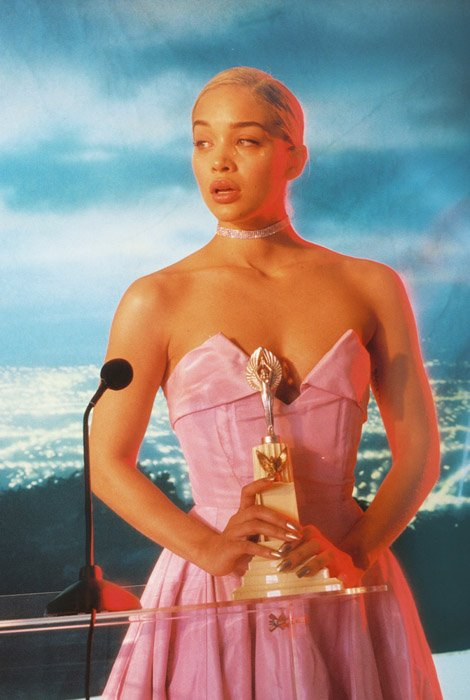 Petra Collins editorial photo of a girl in pink dress holding an award. Famous Portrait Photographers