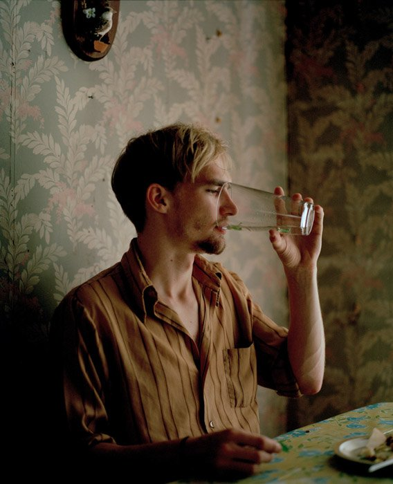 Sasha Arutyunova portrait of a man sitting at a table drinking from a glass. Famous Portrait Photographers