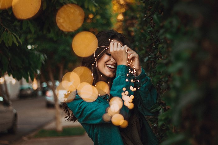 Dreamy portrait of a girl holding fairy lights beside bushes. Self portrait photography tips.