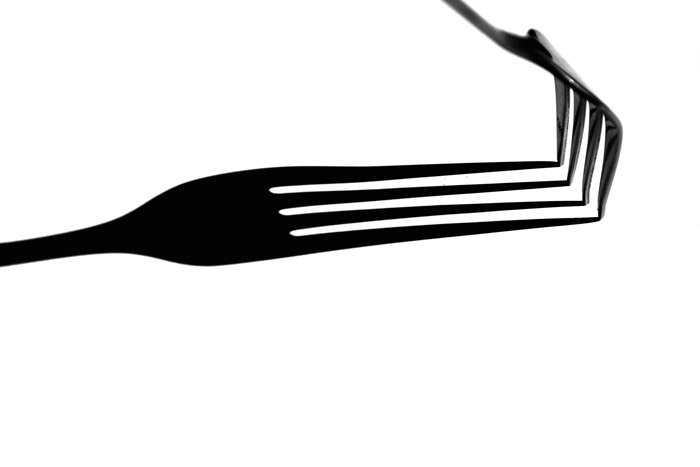A black and white close up photograph of a fork with a strong shadow beneath.