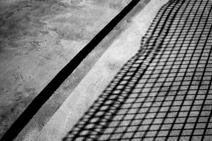 A shadowy black and white photograph of concrete with shadow of a fence.