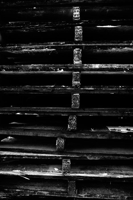 A shadowy black and white photograph of a stack of wooden palettes.