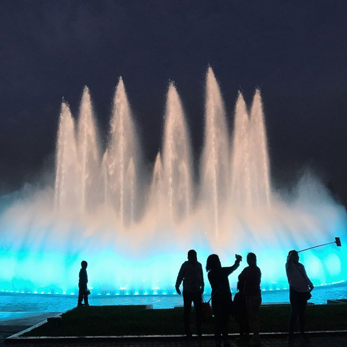 Low light photograph of a beautiful fountain at night with silhouettes of people in the foreground