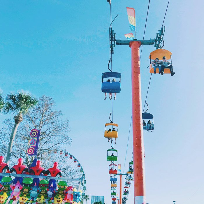 Photograph of funfair rides on a clear blue skies day.