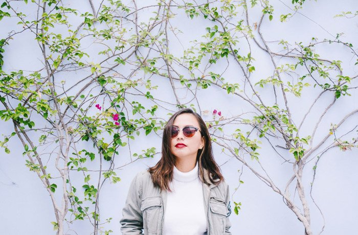 Smartphone photograph of a girl in sunglasses against a white wall.
