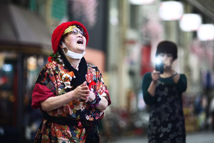 Travel photography of a woman being photographed by another woman with smartphone.