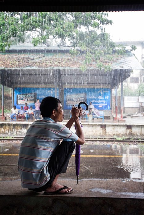 Travel photography of a man with umbrella taking shelter from tropical rain shower.