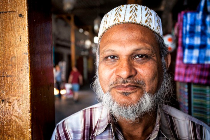 Close up street photography portrait of a man with white beard and hat in a market