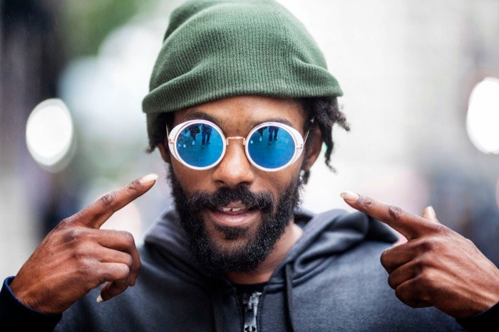 street photography portrait of a man in a green hat pointing to his blue mirrored sunglasses