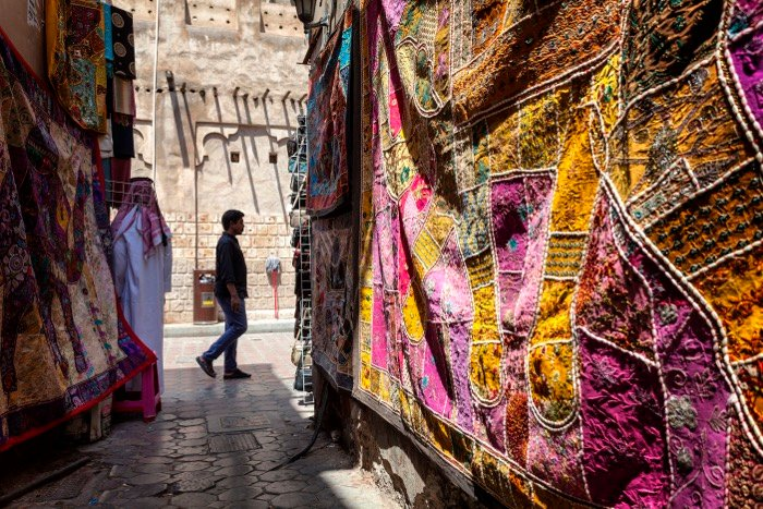 Market scene of a passerby framed by colourful material in the foreground - street photography