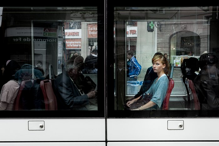 View of a tram window with a young lady looking straight at the camera. Urban photography