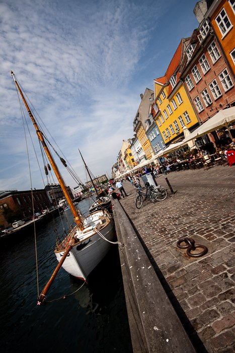 tilted composition photo of the colourful houses, the channel and the restaurants at the Nyhavn canal in Copenhagen