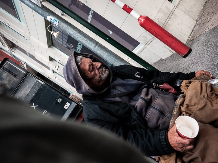 A shot from the hip tilted photograph of a homeless man in a wheelchair holding an empty cup in an urban street scene