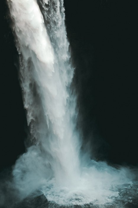 A flowing waterfall hitting a pool of water