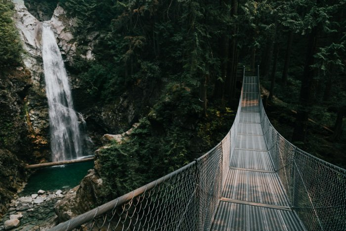 A waterfall in the background of an image of a bridge