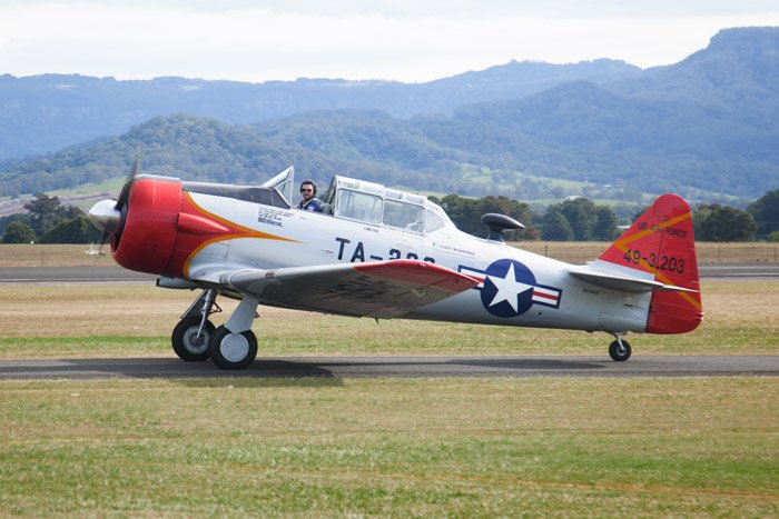 An airshow photography shot of a red and white airplane taxiing on the runway