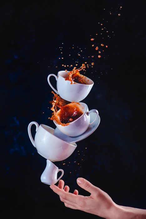 A still life photography shot of balancing cups with coffee splashes on dark background - creative photography ideas