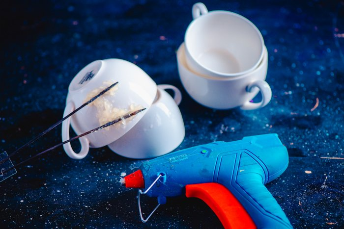 Overhead shot of coffee cups and gluegun on starry blue background for creative photography project