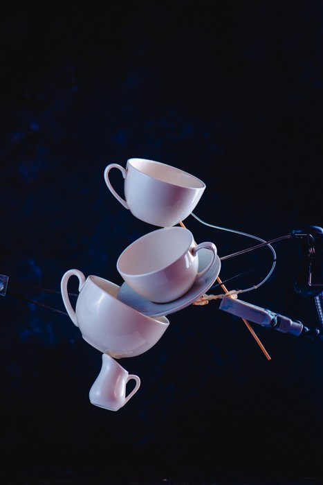 A creative photography idea of balancing falling coffee cups on dark blue background