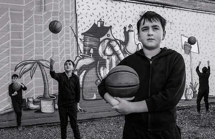Composite photography of four of the same boy playing basketball in front of a mural