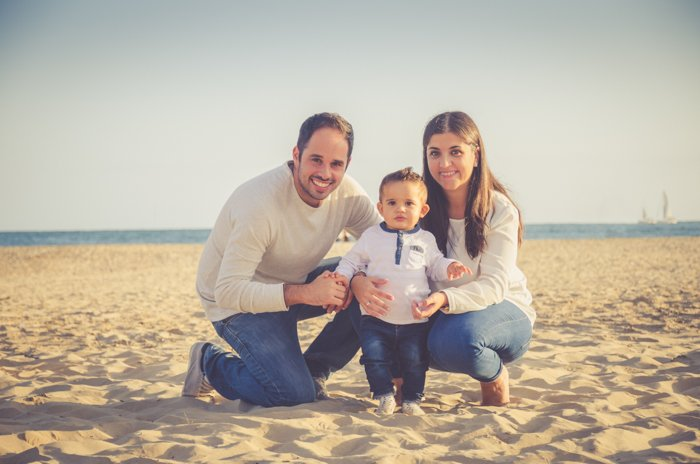 A family photoshoot of a couple and small baby posing on the beach