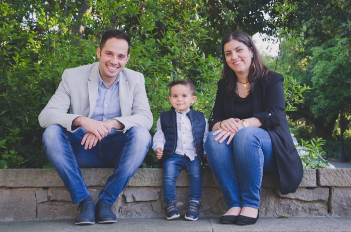 Family portrait photo of a couple and son sitting on a wall outdoors