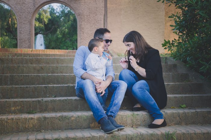 Family portrait photo of a couple and son sitting on outdoor steps
