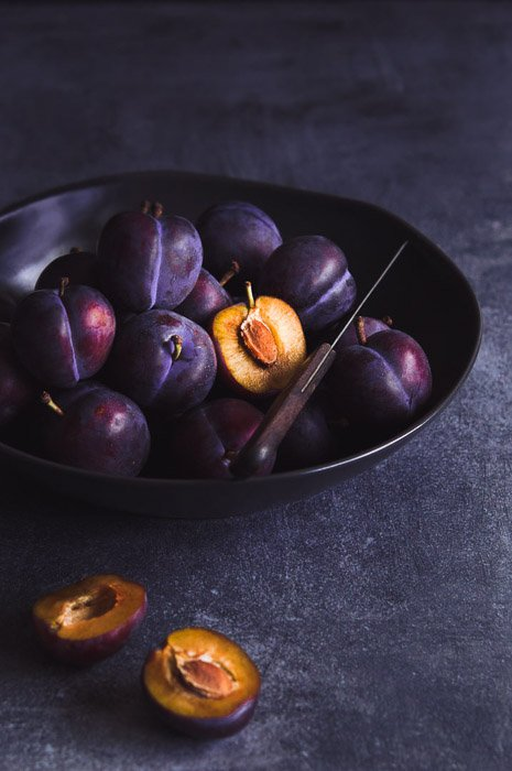 Still life photography of a bowl of plums ion dark background shot with a 60mm macro lenson a cropped sensor camera.