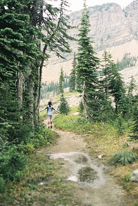 Photo of a girl taking a walk in a lucious forest and mountain landscape