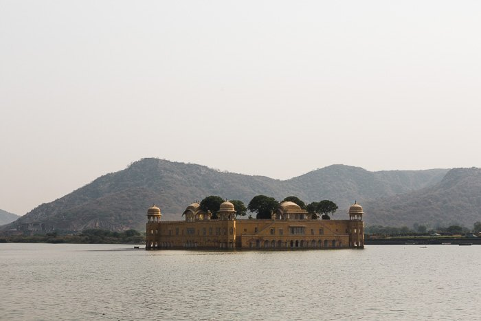 A beautiful indian building surrounded by water and mountains behind