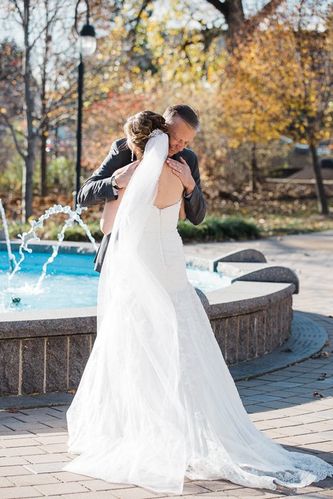 Sweet wedding day moment of a bride hugging her father in front of a fountain