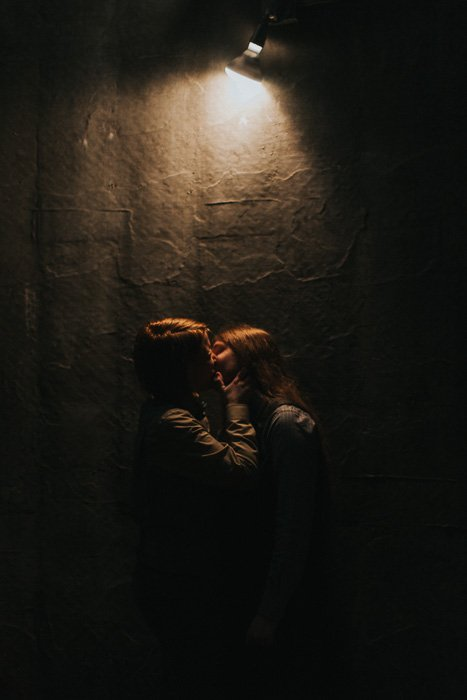 A couple kissing in front of a textured wall with a single light source