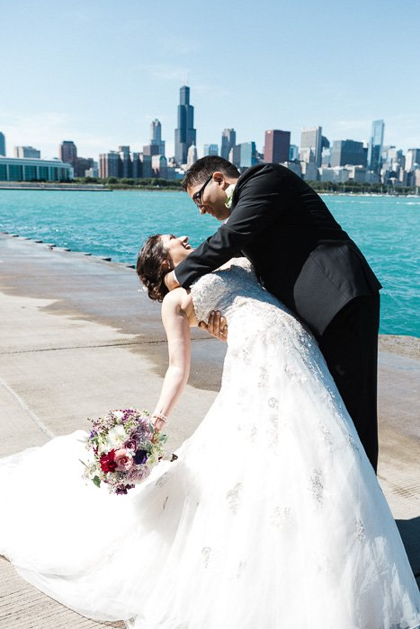 Fun wedding photo of a couple embracing in front of a river