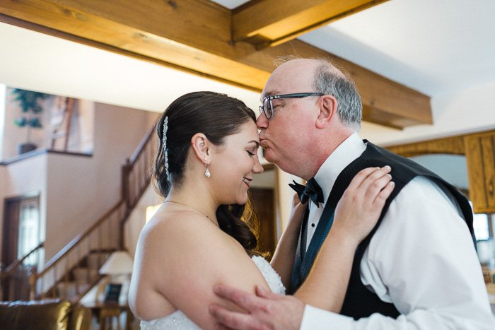 Beautiful moment of father kissing the brides head captured by the wedding photographer