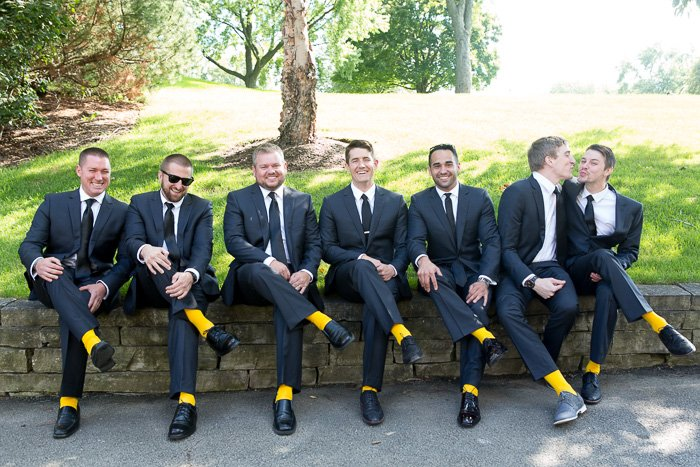 Humorous wedding photo of seven groomsmen sitting on a wall, all wearing yellow socks