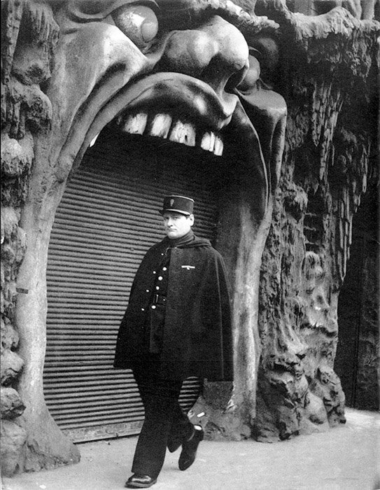 Black and white photo of a man walking by L'Enfer bar in Paris