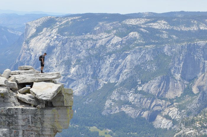 A man standing on the edge of a cliff with an impressive mountain landscape behind him demonstrating size weight balance in photography
