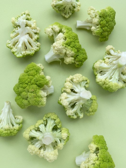 Interesting overhead shot of pale green broccoli on pale green background