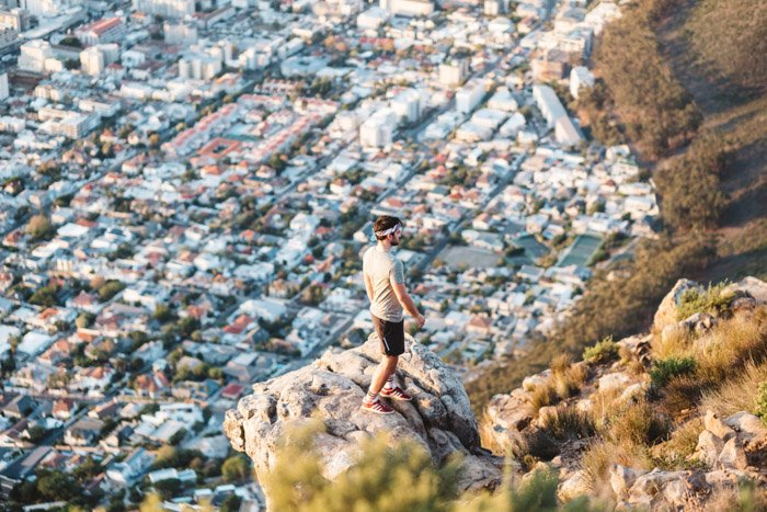 A man standing on the edge of a cliff with an impressive view of houses and buildings below - compositional photography rules