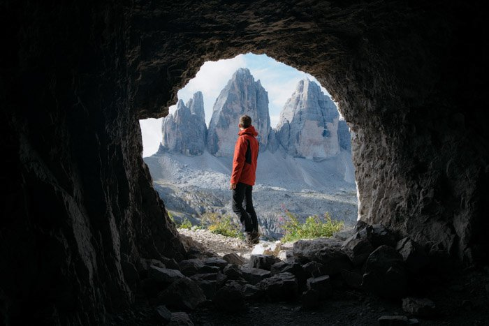 A hiker natural framed by a cave in the foreground