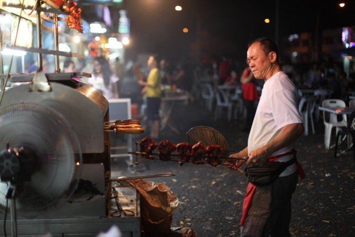 Low light photography of a man cooking meat at an outdoor market.