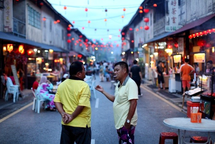 Documentary photography of two men chatting on a busy street
