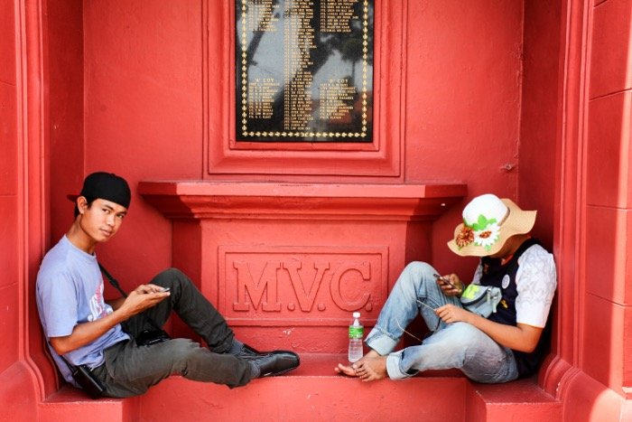 Street photography of two people sitting on a red wall.