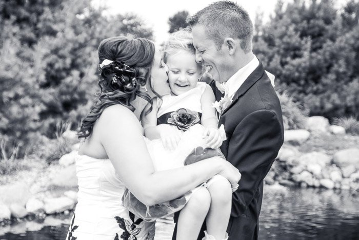 Black and white wedding photo of a couple holding a little girl